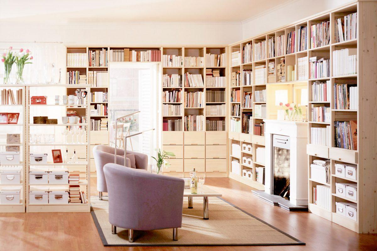 Ein Zimmer mit vielen offenen Regalen gefüllt mit bunten Büchern. In der Mitte des Raumes stehen zwei Sessel vor einem Kamin und einem offenen Raumtrenner.