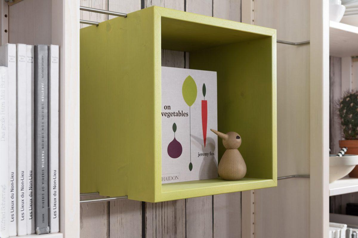 Grüner Kasten gefüllt mit einem Buch und einem Dekohasen aus Holz.